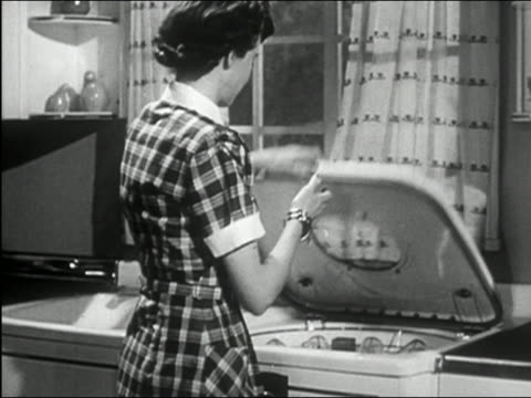 1950 black and white medium shot woman closing dishwasher lid, pushing button to start cycle and turning toward cam - machine part stock videos & royalty-free footage
