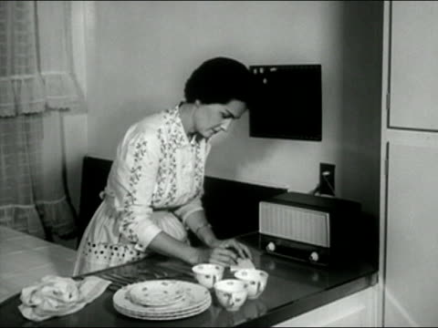 1958 black and white medium shot woman in kitchen writing messages and putting them on message board/ audio - 10 seconds or greater stock videos & royalty-free footage