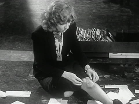 1944 black and white medium shot woman on floor rubbing knees after tripping over open file cabinet and tearing stockings - stockings stock videos & royalty-free footage