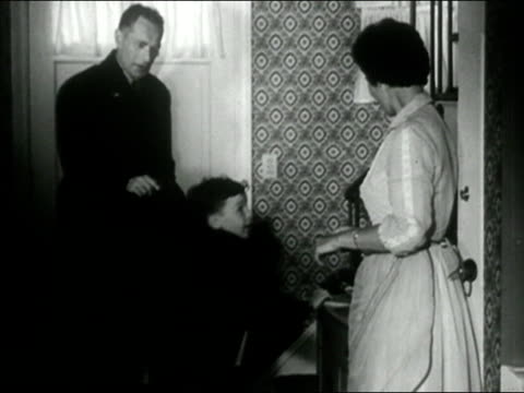 1958 black and white medium shot woman putting coat on young son/ woman kissing young son and husband goodbye before seeing them out the door/ audio - ehemann stock-videos und b-roll-filmmaterial