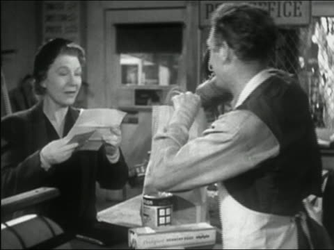 stockvideo's en b-roll-footage met 1941 black and white medium shot woman reading letter to grocer as he bags her items - kruidenier