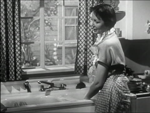 vídeos de stock, filmes e b-roll de 1950 black and white medium shot woman washing dishes, talking and wiping brow - utensílio de cozinha equipamento doméstico