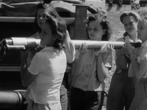 vidéos et rushes de black and white medium shot women carrying gun barrel and connecting it to gun / aberdeen proving ground, maryland - 1942