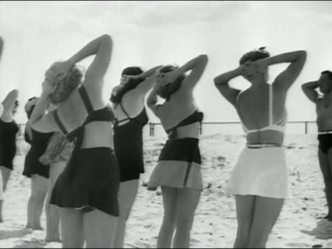 black and white medium shot women taking exercise class led by charles atlas on beach - body building stock-videos und b-roll-filmmaterial