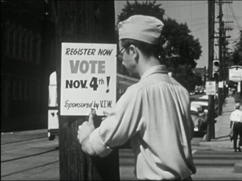 vídeos de stock, filmes e b-roll de 1955 black and white medium shot young man stapling sign on telephone pole at busy intersection urging voter registration - título de eleitor