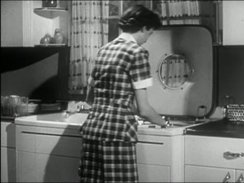 vídeos de stock e filmes b-roll de 1950 black and white medium shot zoom out woman in kitchen loading top-loading dishwasher - lava loiças