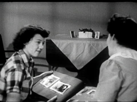 1950 black and white / mother and daughter looking through photo album / audio - photo album stock videos and b-roll footage