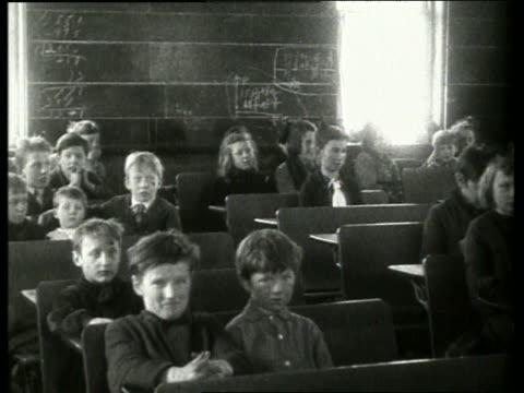 vidéos et rushes de black and white pan of children sitting at desks in classroom / no audio - école