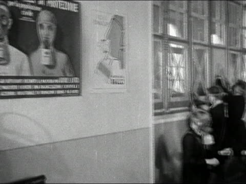 1946 black and white pan poster of man and woman in gas masks in classroom to boys putting on gas masks / italy - 1946 stock videos and b-roll footage