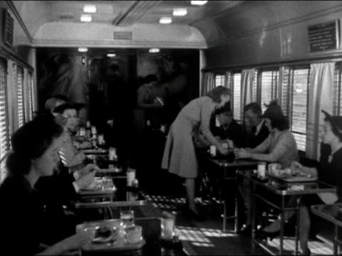 1942 black and white / passengers being served onboard dining car of train / audio - bahnreisender stock-videos und b-roll-filmmaterial