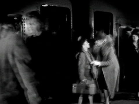 vídeos de stock e filmes b-roll de 1942 black and white / passengers exiting train / woman greeting child passenger with kiss / audio - 1942