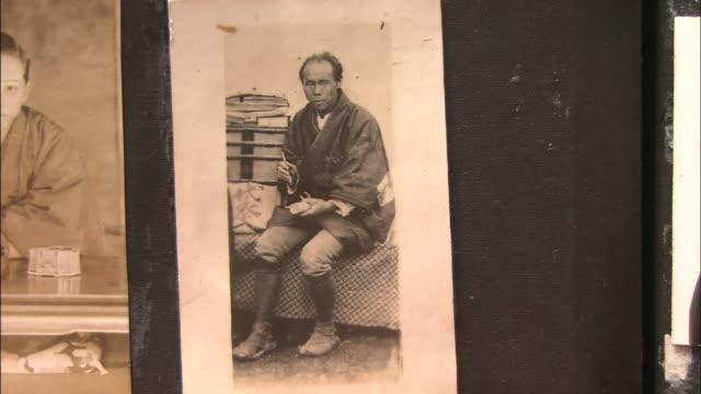 black and white photo of an asian man hangs inside a medicine shop in toyama, japan. - white点の映像素材/bロール