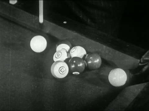 1944 black and white pool stick cueing/ chalk ball curving around stack of balls/ dropping ball in corner pocket - ビリヤード点の映像素材/bロール