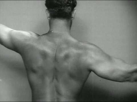 1946 black and white rear view of charles atlas flexing biceps and back muscles / turning around flexing biceps - 1946 stock videos and b-roll footage