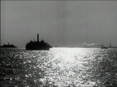 1937 black and white ships and barges sailing through New York harbor at dusk / New York City