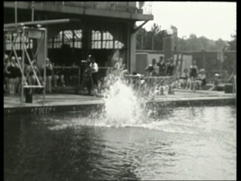 black and white slow motion splash from heavy woman jumping into pool / no - freibad stock-videos und b-roll-filmmaterial