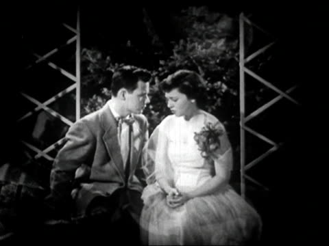 1950 black and white / teenage boy saying, 'I love you,' to teenage girl in garden / audio