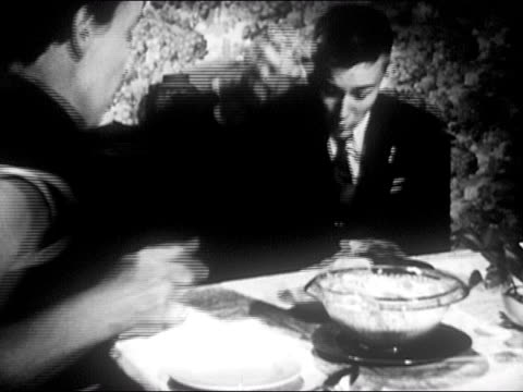 1953 black and white teenage boy taking bowl from woman at dinner table / dropping and breaking it / boy looking sheepish / audio - embarrassment stock videos and b-roll footage