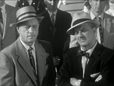 vidéos et rushes de 1956 black and white two men standing in crowd looking at cam with skeptical expressions - indécision