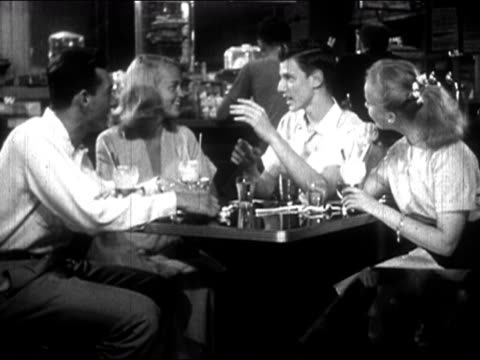 1954 black and white two teenage couples sitting at soda shoppe and talking / boy knocking over milkshake / audio - negative emotion stock videos & royalty-free footage