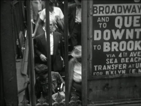 stockvideo's en b-roll-footage met 1949 black and white view through bars of commuters entering subway / new york city - 1949
