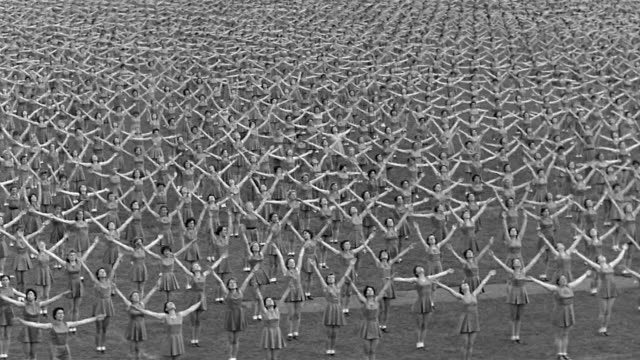 1955 black and white wide shot 11,000 women performing synchronized calisthenics in mass assembly / switzerland - conformity stock videos & royalty-free footage