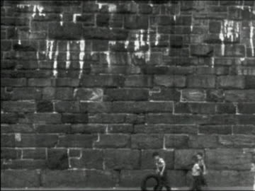 vidéos et rushes de 1949 black and white wide shot boys walking by enormous stone wall as one boy rolls tire / new york city - 1949