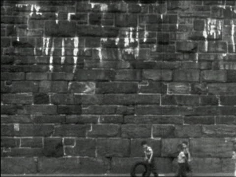 1949 black and white wide shot boys walking by enormous stone wall as one boy rolls tire / New York City