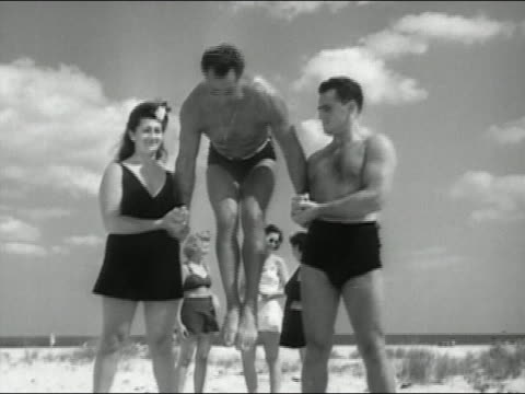 vídeos y material grabado en eventos de stock de black and white wide shot charles atlas performing handstand while balancing on people's hands at beach - bañador de hombre