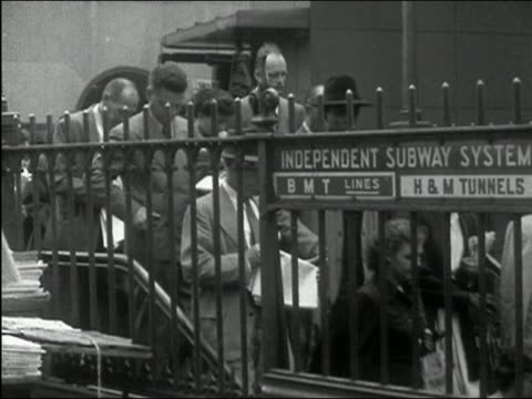 stockvideo's en b-roll-footage met 1949 black and white wide shot commuters walking down steps to bmt subway line / new york city - 1949