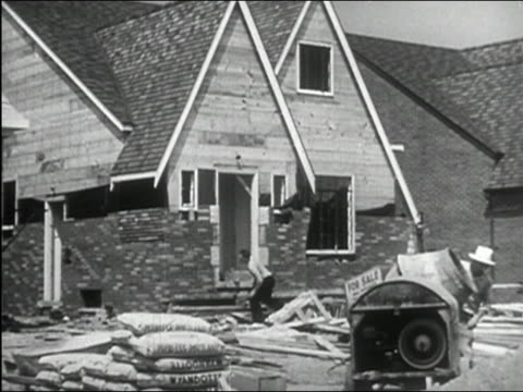 1950 black and white wide shot construction workers standing in front of gutted building with cement mixer in foreground - cement mixer stock videos & royalty-free footage