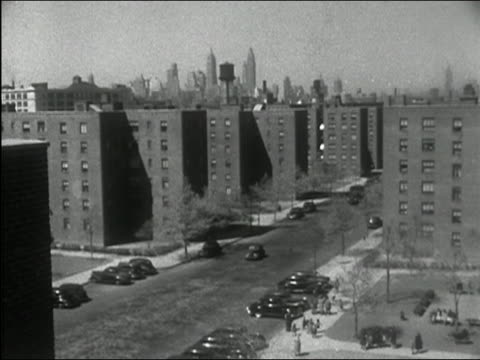1949 black and white wide shot high angle housing project with cars driving down street and skyline in background / new york city - housing difficulties stock videos & royalty-free footage