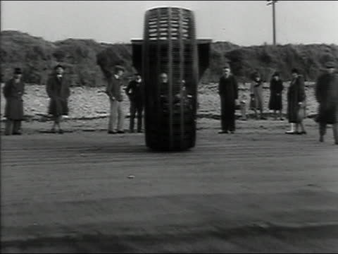 1932 black and white wide shot inventor, dr. j. a. purves of taunton, england, driving dynasphere single-wheeled vehicle on beach / weston-super-mare, england - scoperta video stock e b–roll