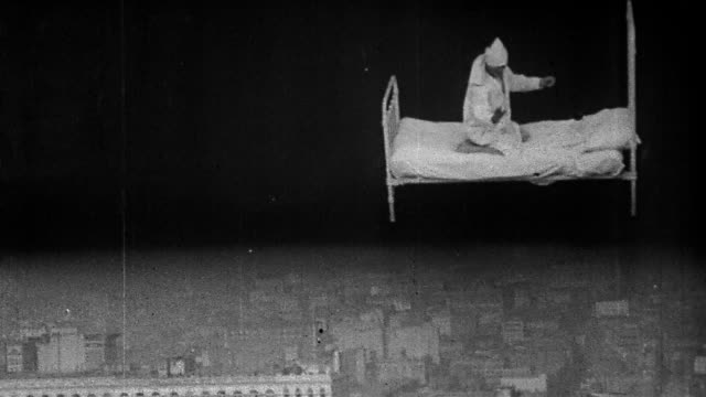 "1906 black and white wide shot man in bed flying over manhattan / writhing and steering / ""dream of a rarebit fiend"" /nyc - anno 1906 video stock e b–roll"
