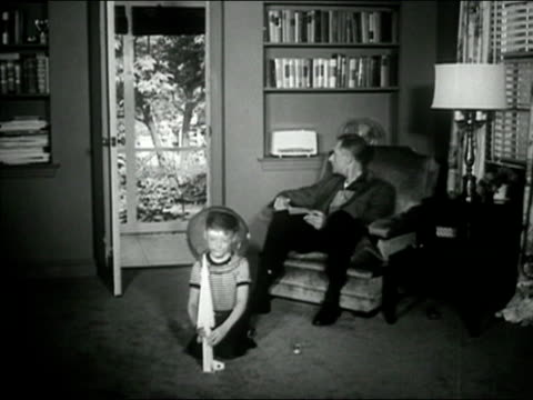 1958 Black and white wide shot man reading in chair in living room as boy puts on space helmet/ boy playing with toy rocket/ AUDIO