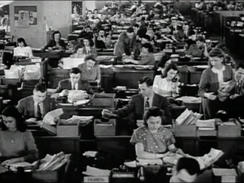 vídeos de stock e filmes b-roll de 1947 black and white wide shot men and women working at desks in huge open plan office / audio - estilo retro
