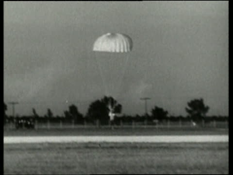 black and white wide shot of man with parachute landing on air field / no audio - only mid adult men stock videos & royalty-free footage