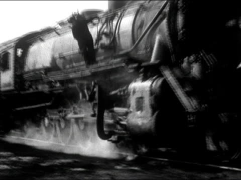 vídeos de stock e filmes b-roll de 1942 black and white / wide shot of steam locomotive traveling on track / medium shot of wheels of locomotive / audio - locomotiva a vapor