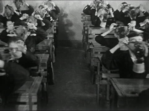 1946 black and white wide shot pan boys putting on gas masks in classroom / Italy