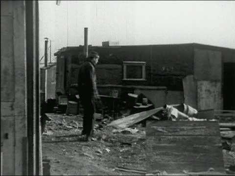 1937 black and white wide shot pan man walking and spitting in shantytown near Manhattan / PAN waterfront / New York City