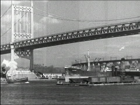 1937 black and white wide shot ships passing under Triborough Bridge / pan Hell Gate Bridge in background / New York City