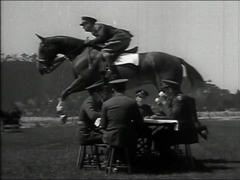 1934 black and white wide shot slow motion us 11th cavalry riders jumping over fellow officers drinking at table /california - cavalry stock videos & royalty-free footage