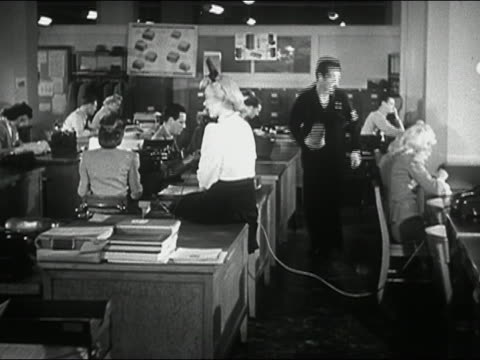 1944 black and white wide shot woman talking on phone in office / man tripping over phone cord and dropping documents