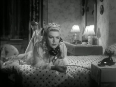 1941 black and white wide shot young woman lying on top of bed and talking into telephone