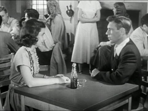 1950 black and white young man sitting down at table / arguing with young woman / girl walking away
