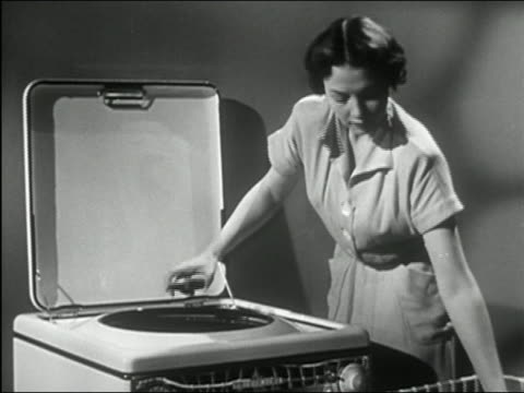 1950 black and white zoom out medium shot woman filling washing machine / adding soap and pushing button to start cycle