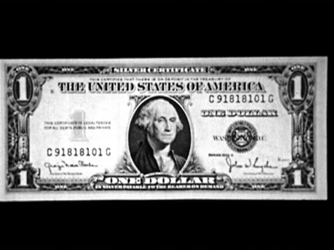 1953 Black and white zoom out zoom in on US dollar bill against black background / AUDIO