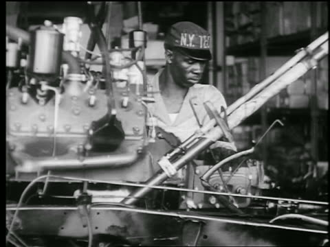 stockvideo's en b-roll-footage met b/w 1945 black auto worker lowers engine onto transmission in car assembly line / educational - productielijn werker