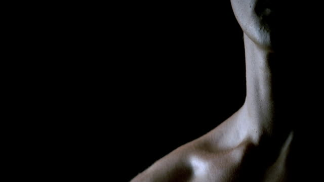CU PAN black background to man's face in shadow/ TD muscular chest and abdominal muscles/ New York, New York