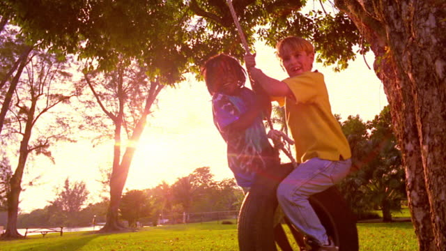 ms black boy + blonde boy swinging on tire swing in park - tyre swing stock videos & royalty-free footage
